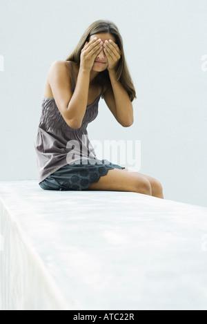 Teenager-Mädchen sitzen, die Augen mit Händen - Stockfoto