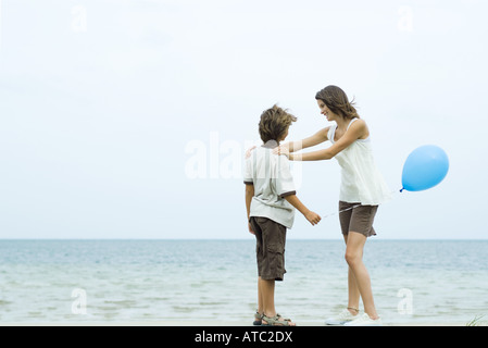 Teenager-Mädchen am Strand, stehen Hände auf ihren Bruder Schultern, junge Ballon halten Stockfoto