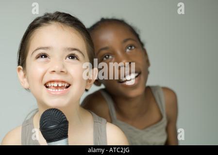 Zwei junge Mädchen singen in Mikrofon zusammen, lächelnd und das Nachschlagen - Stockfoto