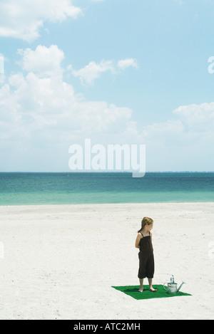 Mädchen stehen auf dem Platz des Kunstrasens am Strand, neben dem Gießen kann, erhöhte Ansicht - Stockfoto