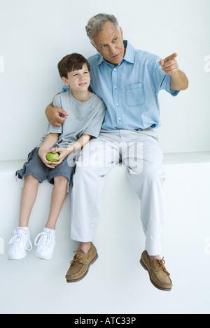 Mann, sitzend mit Arm um Enkels Schultern zeigend, beide wegschauen - Stockfoto