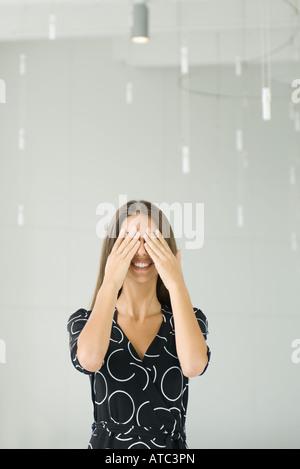 Teenager-Mädchen Abdeckung Augen mit den Händen, lächelnd, Frontansicht - Stockfoto