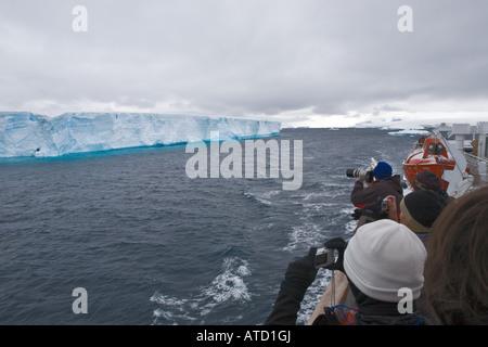 Gesichtslose Touristen fotografieren riesigen Eisberg mit blauen Reflexionen von Schiff im antarktischen Meere - Stockfoto