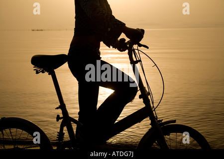 Silhouette der jungen Frau See Radfahren - Stockfoto