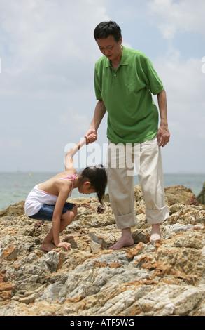 Reifer Mann hilft seiner Enkelin auf einem Felsen - Stockfoto