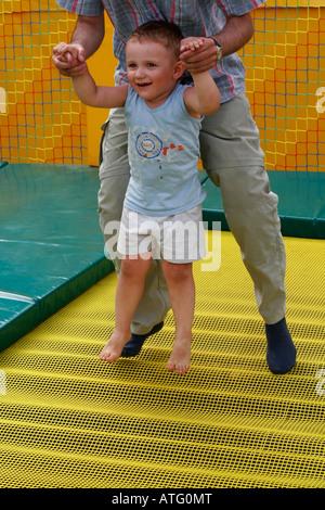 Vater und Sohn spielen am Spielplatz, einen 3 - Jahre alten junge, springen auf einem Trampolin - Stockfoto