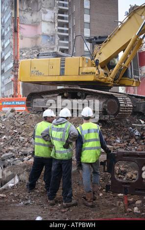 Bauarbeiter diskutieren Arbeit auf den Abriss einer Wohnsiedlung. - Stockfoto