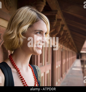 Nahaufnahme einer jungen Frau lächelnd und wegsehen, Taj Mahal, Agra, Uttar Pradesh, Indien - Stockfoto
