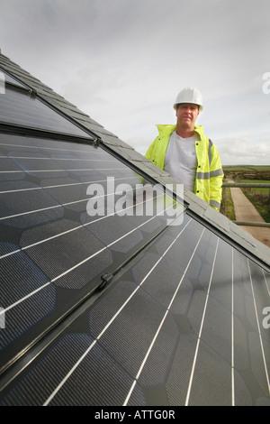 Mann mit einem Herde Hut und Hi-Vis Jacke Inspektion eines Photovoltaik-Bereichs - Stockfoto