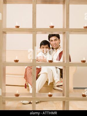 Junger Mann mit seinem Sohn auf einer Couch sitzend - Stockfoto