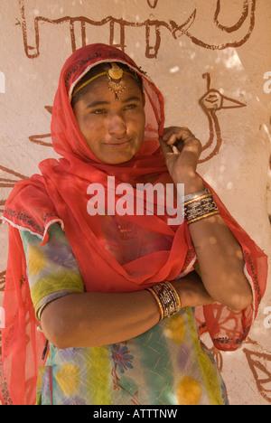 Schöne junge indische Frau geschmückt mit Schmuck und trägt einen Sari vor einer Wand mit primitive Malerei verziert - Stockfoto