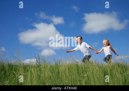 Junge & Mädchen laufen in hohe Gräser - Stockfoto