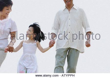 Ehepaar und ein junges Mädchen Hand in Hand - Stockfoto