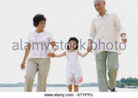 Ehepaar und ein junges Mädchen im Freien am Strand Hand in Hand - Stockfoto