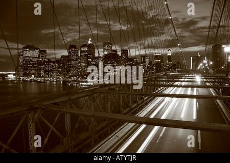 Die Fahrbahn auf der Brooklyn Bridge mit der Skyline von Manhatten hinter. - Stockfoto