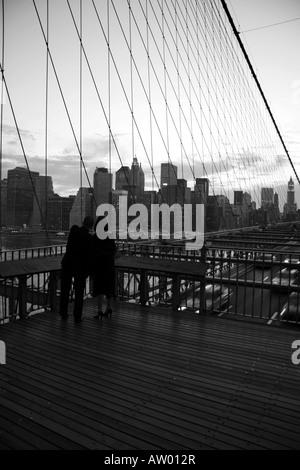 Ein paar auf der Brooklyn Bridge, die Manhattan Skyline hinter. - Stockfoto