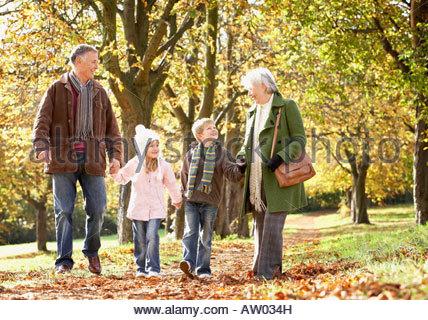 Paar im freien Hand in Hand mit zwei kleinen Kindern in einem park - Stockfoto