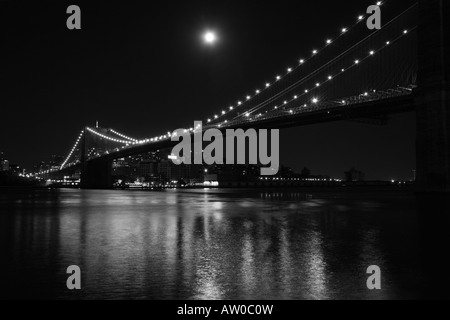 Eine Nachtansicht in schwarz und weiß von der Brooklyn Bridge, New York von unten Franklyn D. Roosevelt Drive, Manhattan. - Stockfoto