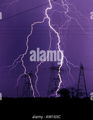 Blitzeinschläge vor einem dunklen lila Himmel in der Nähe von Stromleitungen und Strommasten oder elektrische Türme - Stockfoto
