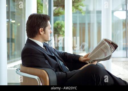 Mann sitzt im Sessel mit einem Magazin in der hand - Stockfoto