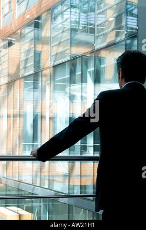 Mann am Fenster in einem Bürogebäude - Stockfoto
