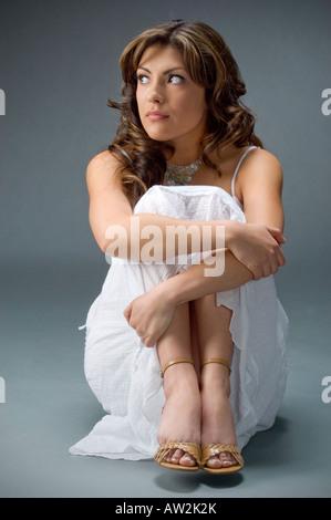 bescheidene junge Frau sitzt Sitzposition [nicht Blick in die Kamera] - Stockfoto