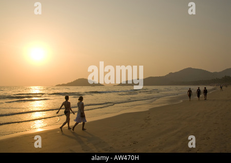 Menschen zu Fuß entlang Palolem Beach in Goa in Südindien bei Sonnenuntergang - Stockfoto