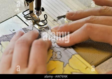 Hände in der Nähe von einer Nähmaschine Fuß in Bewegung - Stockfoto