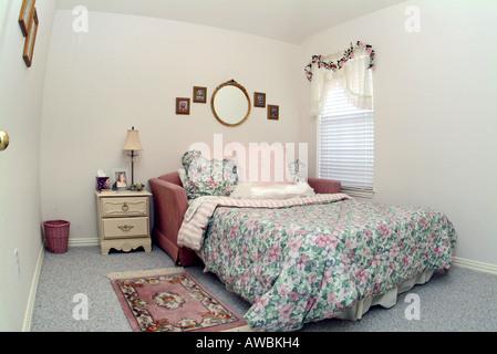 Blick auf ein gemütliches Bett mit einem floralen Bettdecke - Stockfoto