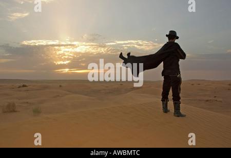 Ein Reiseleiter gekleidet wie ein Reiter den Sonnenuntergang in der Wüste Sahara in der Nähe der Oase von Ksar Ghilane, - Stockfoto