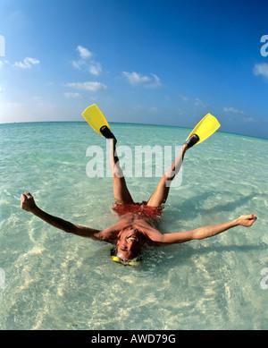 Junger Mann tragen flossen Verlegung im flachen Wasser, Urlaub, Malediven, Indischer Ozean - Stockfoto