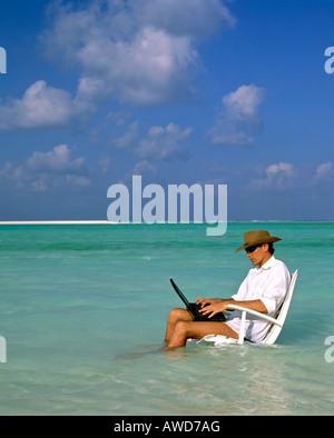 Junger Mann mit Laptop sitzen im Liegestuhl, Arbeit und Entspannung, Urlaub und Stress, Malediven, Indischer Ozean - Stockfoto