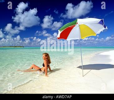Junge Frau, die Verlegung in seichtem Wasser, Regenschirm, Paradiesstrand, Malediven, Indischer Ozean - Stockfoto