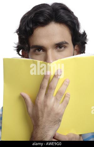 ANG200513 Teenager halten gelbes überdachte Buch vor sein Gesicht Herr 687T - Stockfoto