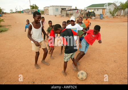 Kinder spielen Fußball auf unbefestigte Straße, Sehitwa, Botswana, Afrika - Stockfoto