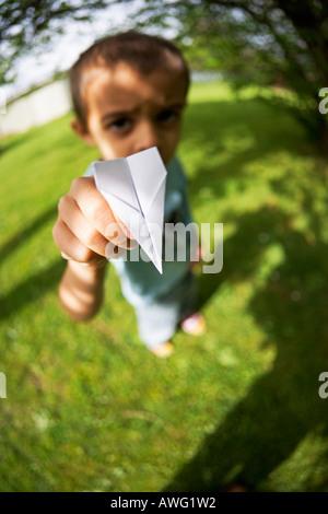 Junge hält Papierflieger in der hand - Stockfoto