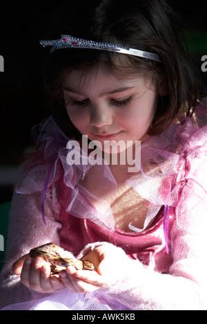 Junges Mädchen in Prinzessin Kostüm hält eine Schlange Reptil auf der Kinder s pädagogische Geburtstagsfeier in - Stockfoto