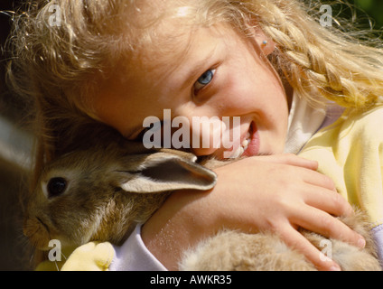 Mädchen umarmt Kaninchen, close-up - Stockfoto