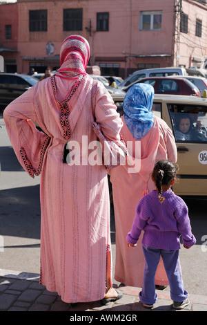 Zwei Frau tragen rosa djellabas und ein kleines Mädchen am Straßenrand in der historischen Medina von Marrakesch, - Stockfoto