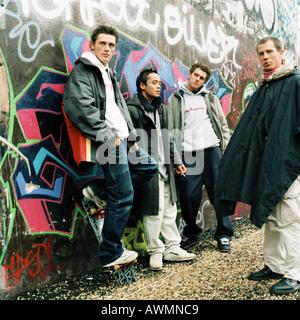 Vier junge Männer in Stadtstraße, drei Graffitiwand gelehnt - Stockfoto