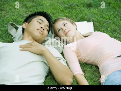 Junges Paar im Rasen, Kopf an Kopf liegen - Stockfoto