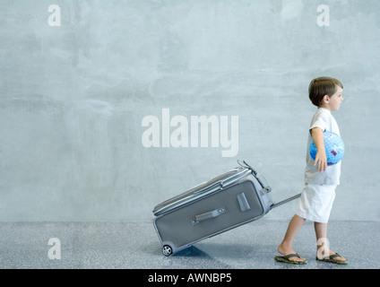 Jungen ziehen Koffer und Globus unter Arm tragen - Stockfoto