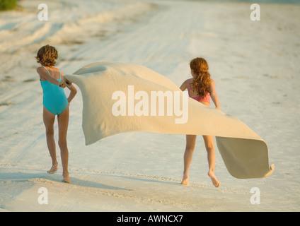 Zwei Mädchen am Strand laufen halten Decke draußen im wind - Stockfoto