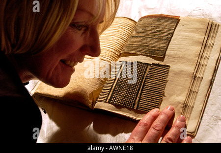 Eine Frau nimmt einen genaueren Blick auf ein altes Buch der historischen Textilproben - Stockfoto