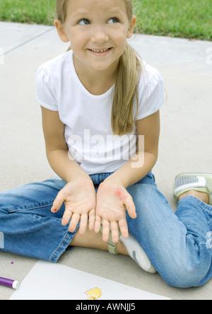 Mädchen sitzen mit der Erstellung von Materialien, Markierungen auf Handflächen zeigen - Stockfoto