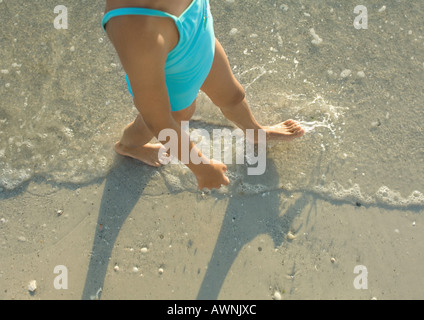 Mädchen zu Fuß in surf - Stockfoto