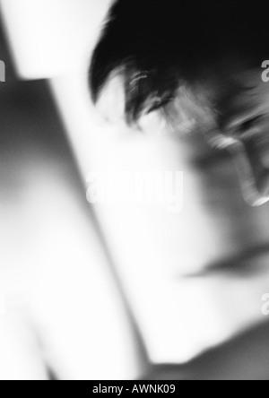 Teil des Mannes Gesicht und Haar, mehrdeutige Formen im Hintergrund unscharf, schwarz und weiß. - Stockfoto