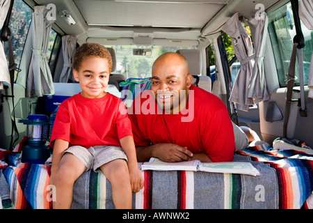 Vater und Sohn sitzen im Kofferraum des Autos mit Campingausrüstung - Stockfoto