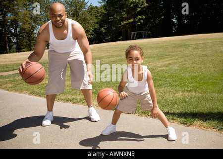 Vater und Sohn dribbling Basketbälle - Stockfoto