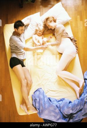 Mann, eine schwangere Frau und Kind auf Bett, erhöhten Blick - Stockfoto